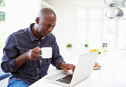 Man sitting drinking coffee while looking at laptop