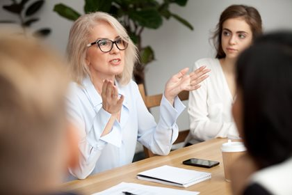 Woman with glasses in a meeting - FirstService Residential